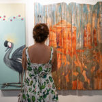 young woman looking at paintings on wall