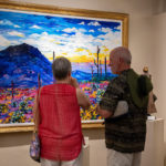 elderly man and woman looking at painting