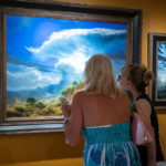 2 women looking at landscape painting