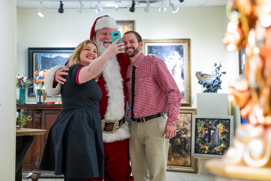 a young couple takes a selfie with Santa Claus in an art gallery