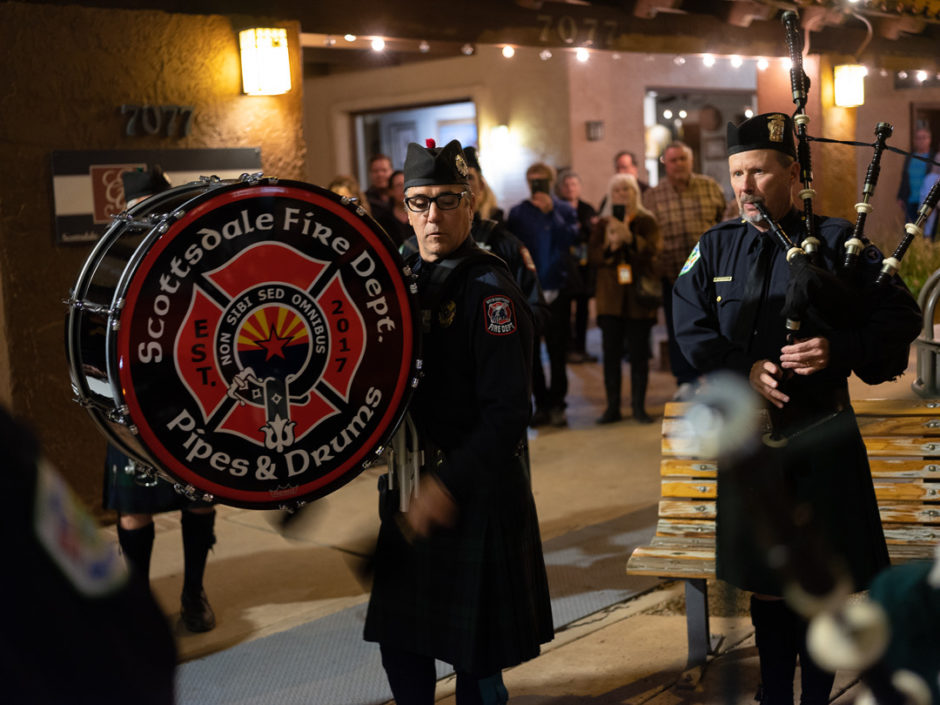 Color photo night scene of 2 policement in kilts marching. One carries a large vertical drum and the other bagpipes while people look on.
