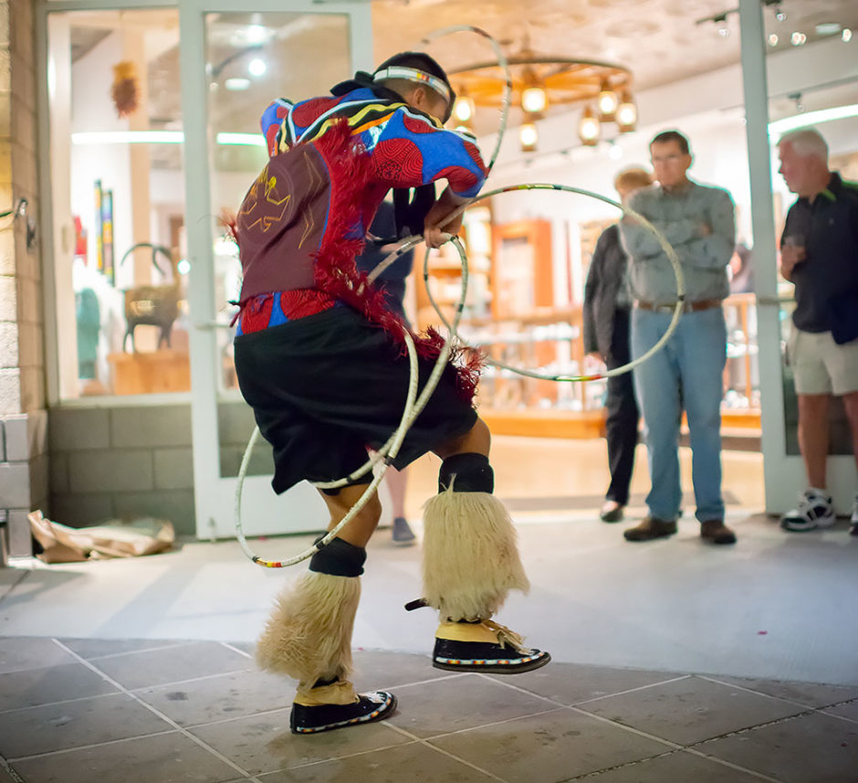 Native American male in fancy regalia hoop dancing in front of a store